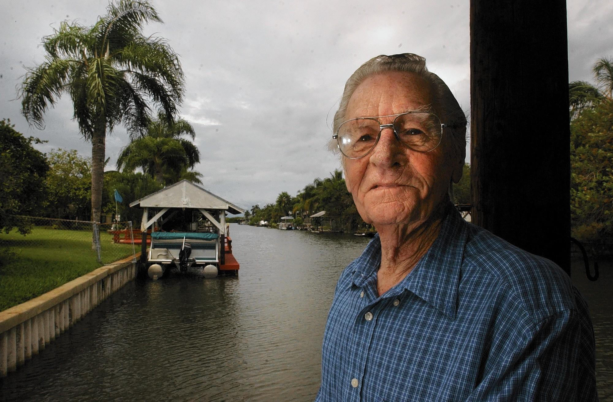 Patrick Smith, author of numerous books on fictional Florida history, at his home. Shown here in front of the canal behind his home on Merritt Island.
