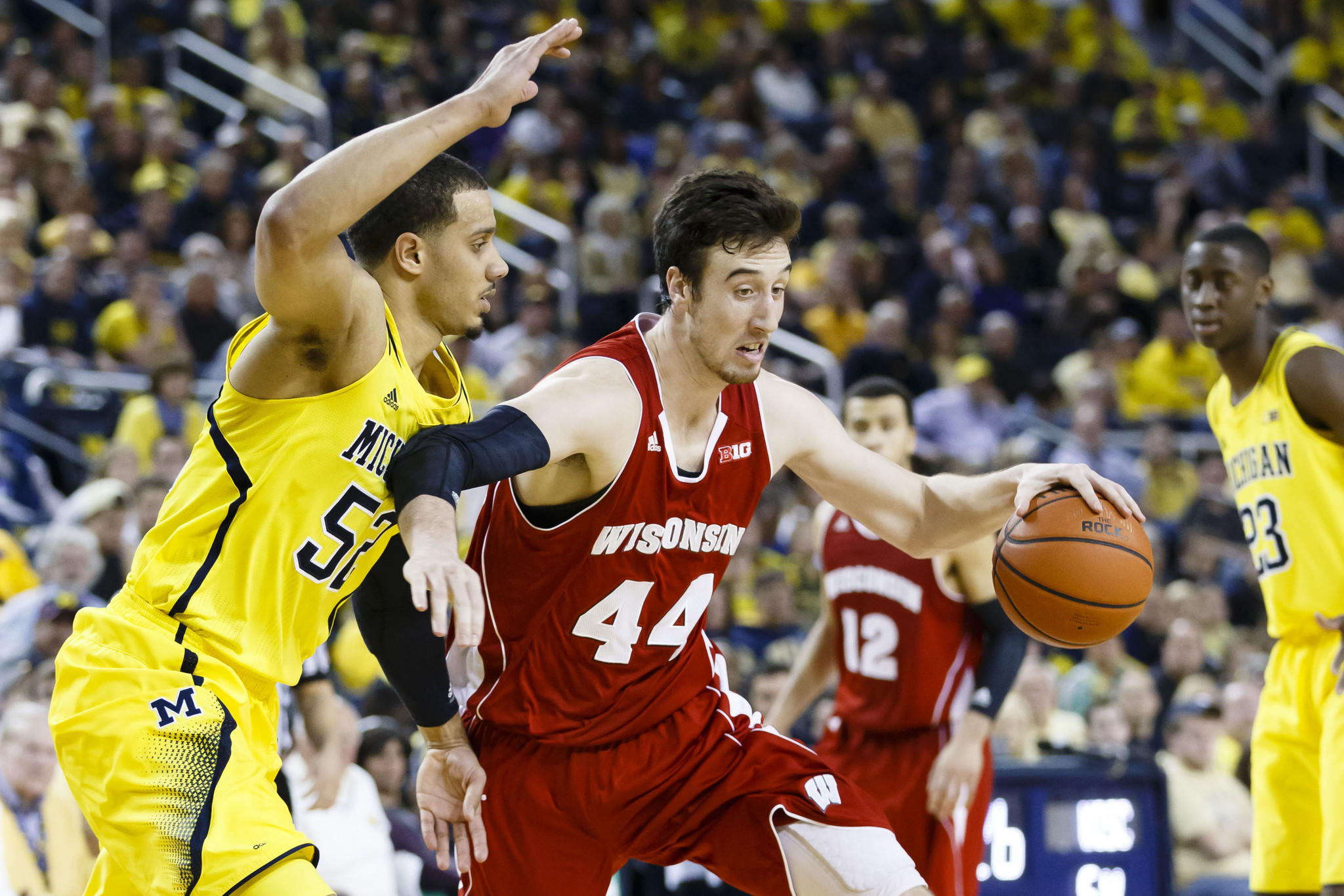 Wisconsin's Frank Kaminsky dribbles the ball around Michigan's Jordan Morgan in the second half at Crisler Arena.