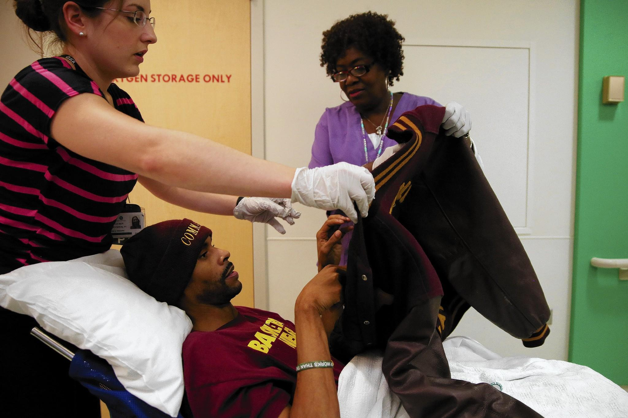 Shawn Harrington, who was shot in late January while driving his daughter to school in Chicago, is helped by physical therapist Lauren Seymour, left, and registered nurse Sharon Riggins before being taken for an MRI this month at the Rehabilitation Institute of Chicago.