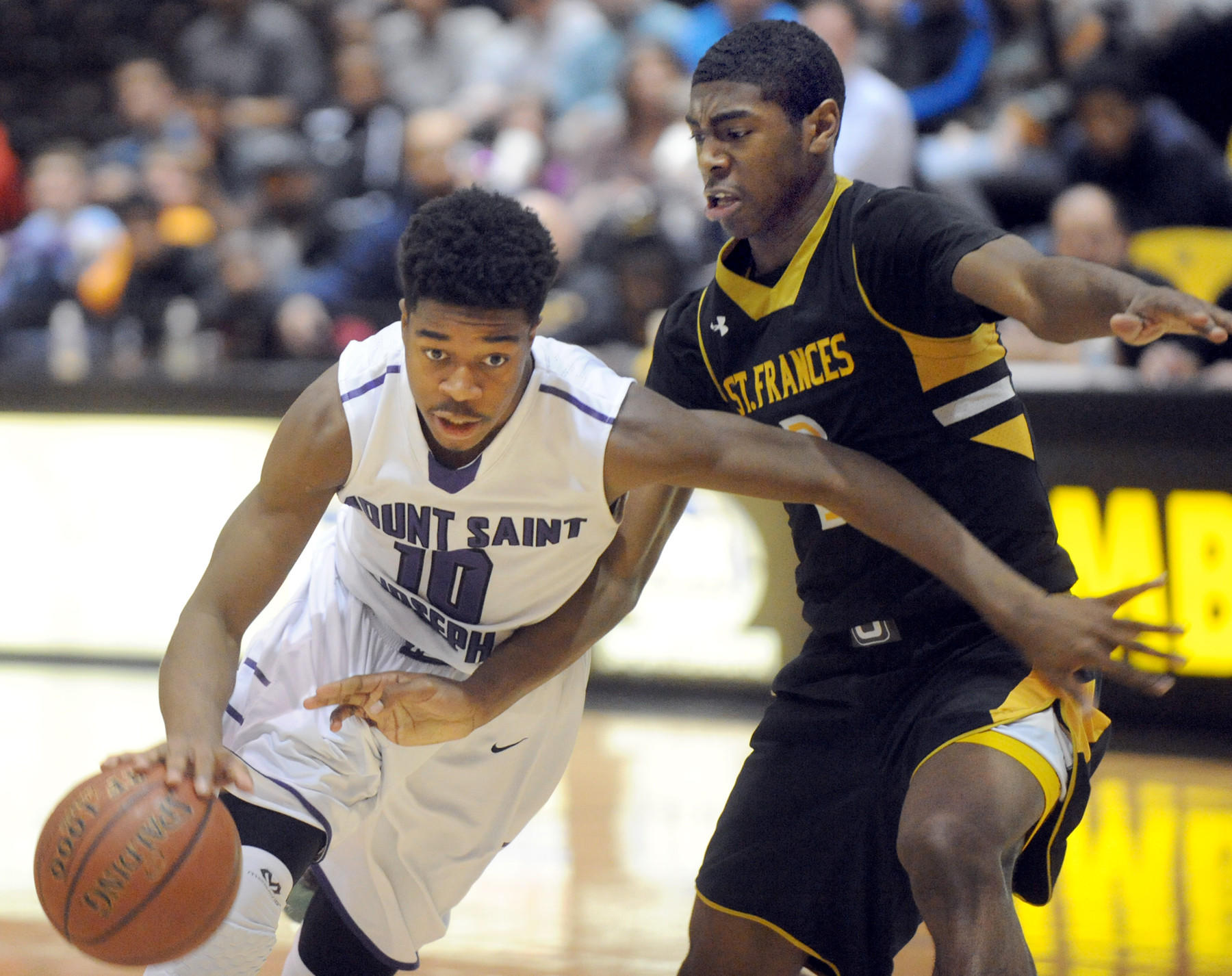 Mount St. Joseph's Jordan McNeil holds onto the ball as St. Frances' Jared Hamilton defends.