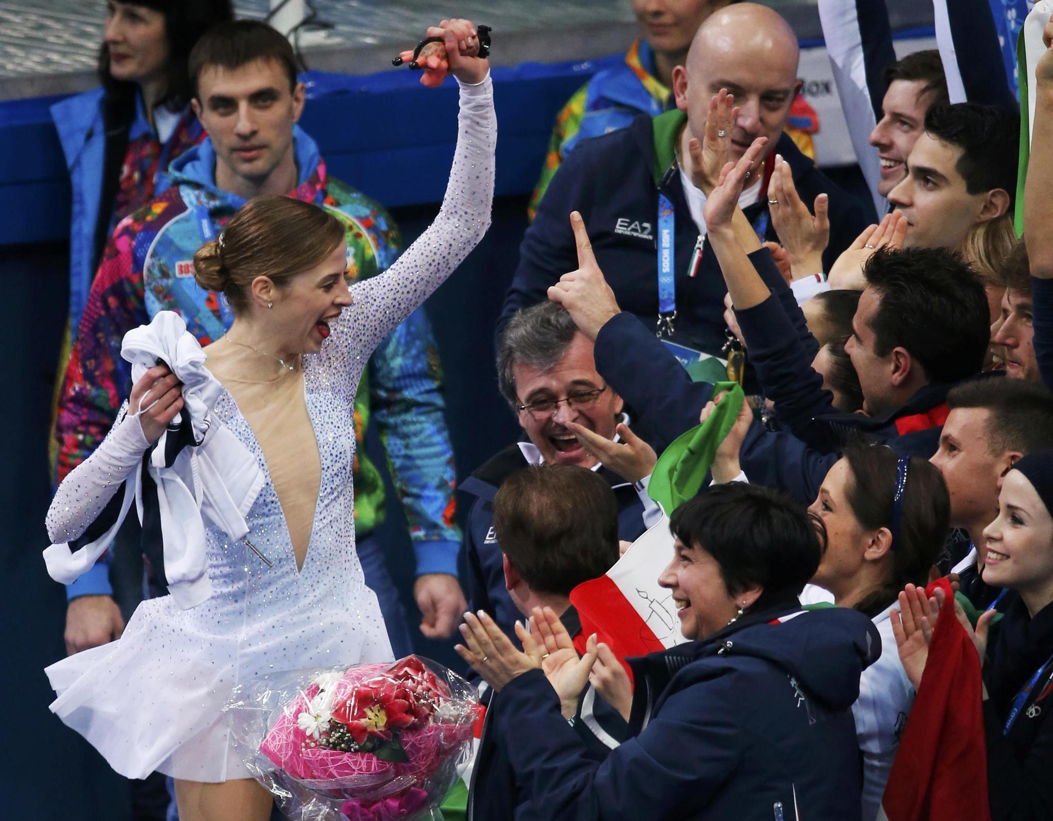 Carolina Kostner (white dress) exults after her strong skate in team event short program.