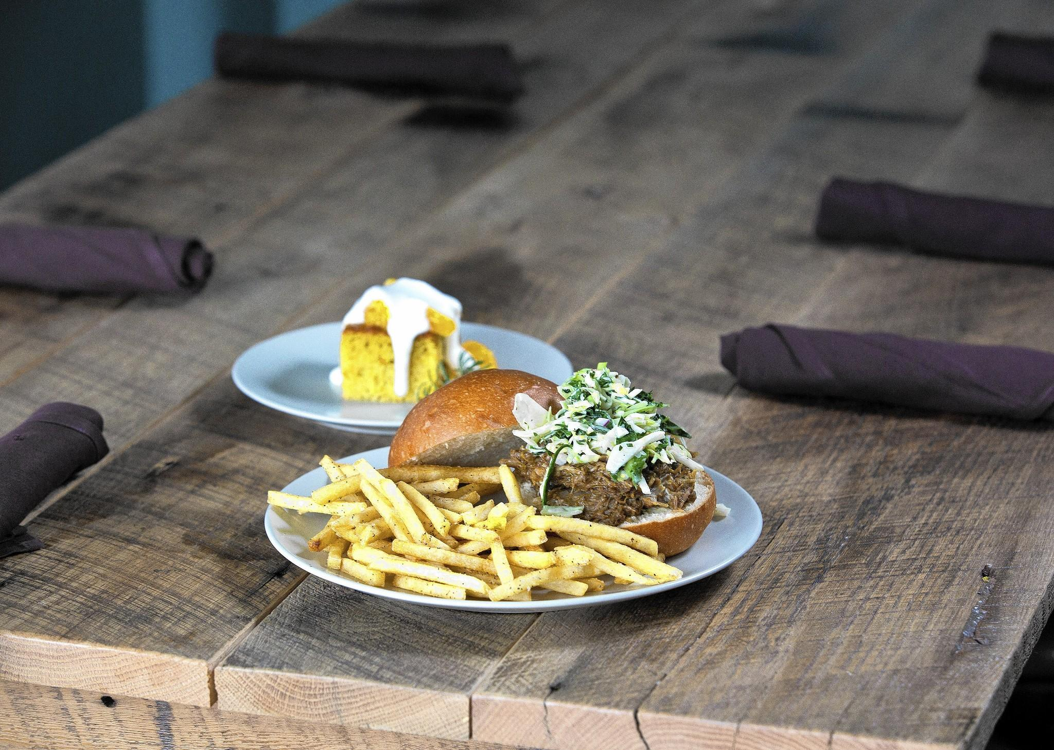 The Strand serves Porkzilla sandwich with fries and seasonal coleslaw (front) and an olive-oil cake.