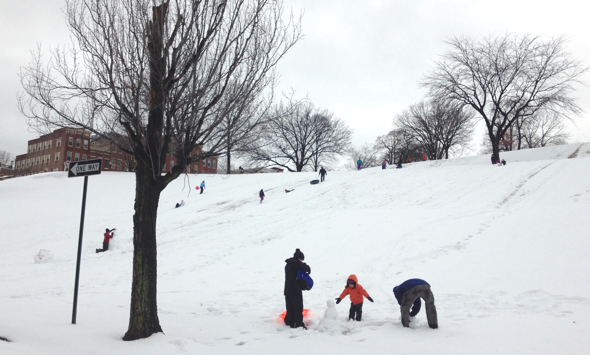 "Kids enjoy their ""snow day"" sledding and building snowmen on Federal Hill."