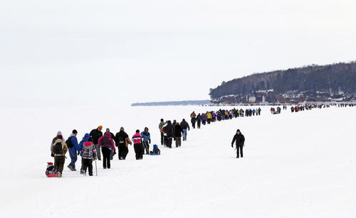 Sightseers trek across a frozen expanse of Lake Superior, the world's largest freshwater lake, to the sea caves of the Apostle Islands National Lakeshore near Cornucopia, Wisconsin February 15, 2014. According to the National Oceanic and Atmospheric Administration (NOAA) Great Lakes Environmental Research Laboratory, about 94% of Lake Superior is covered with ice, enabling thousands of people to visit the islands on foot for the first time since 2009. The Great Lakes, which contain one fifth of the world's surface fresh water, are 88% covered with ice.