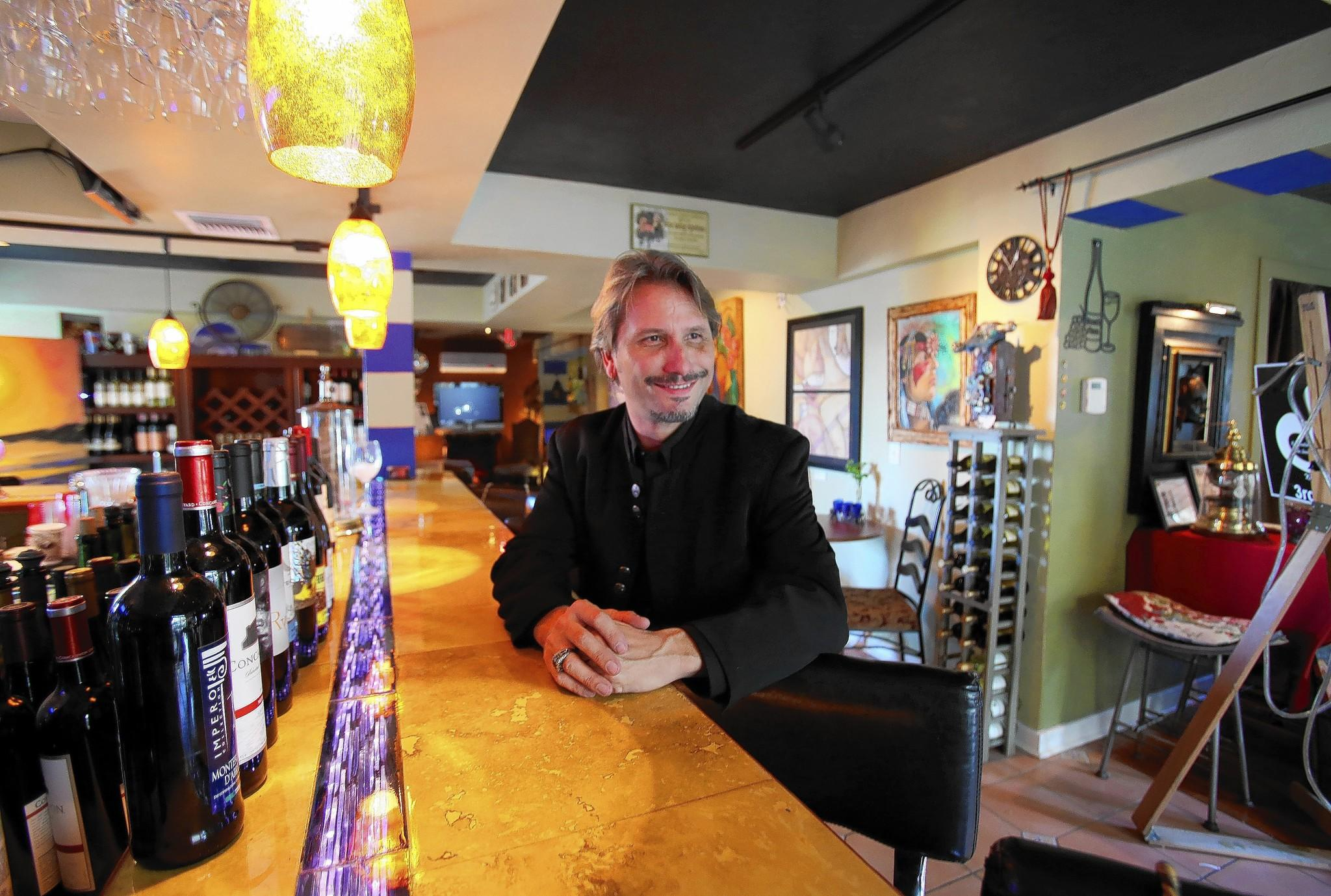Norman Rinne sits at the bar in Norm's Palette, a combination art gallery and bar in the heart of Mount Dora, on Friday, November 6, 2013.