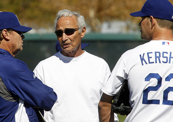 Former Dodger great Sandy Koufax chats with pitching coach Rick Honeycutt and ace Clayton Kershaw during spring training last year.
