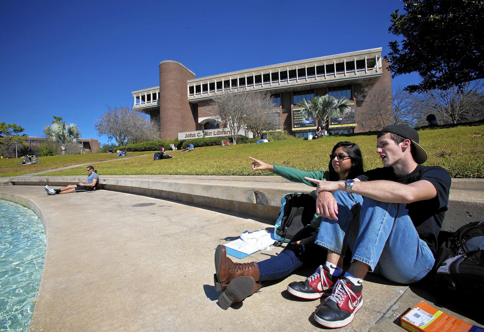 UCF students Chuck Flowers and his girlfriend Marly Santillan take advantage of the gorgeous weather while sitting by the reflecting pond on campus on Monday, February 17, 2014.