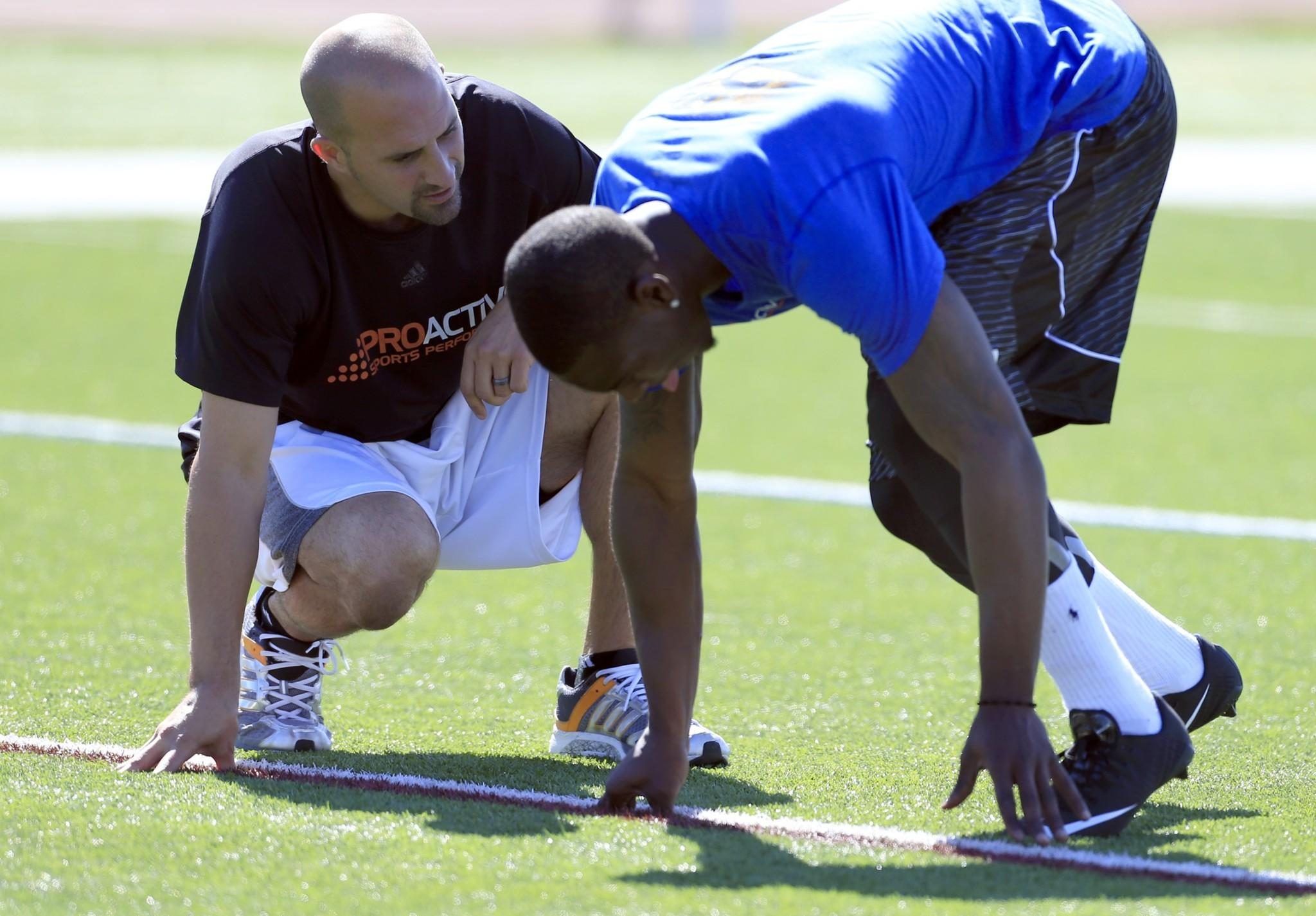 Marqise Lee, an All-American receiver while at USC, works on his starting form for the 40-yard dash with Proactive Sports Performance trainer Ryan Capretta during a training session at Laguna Hills High.