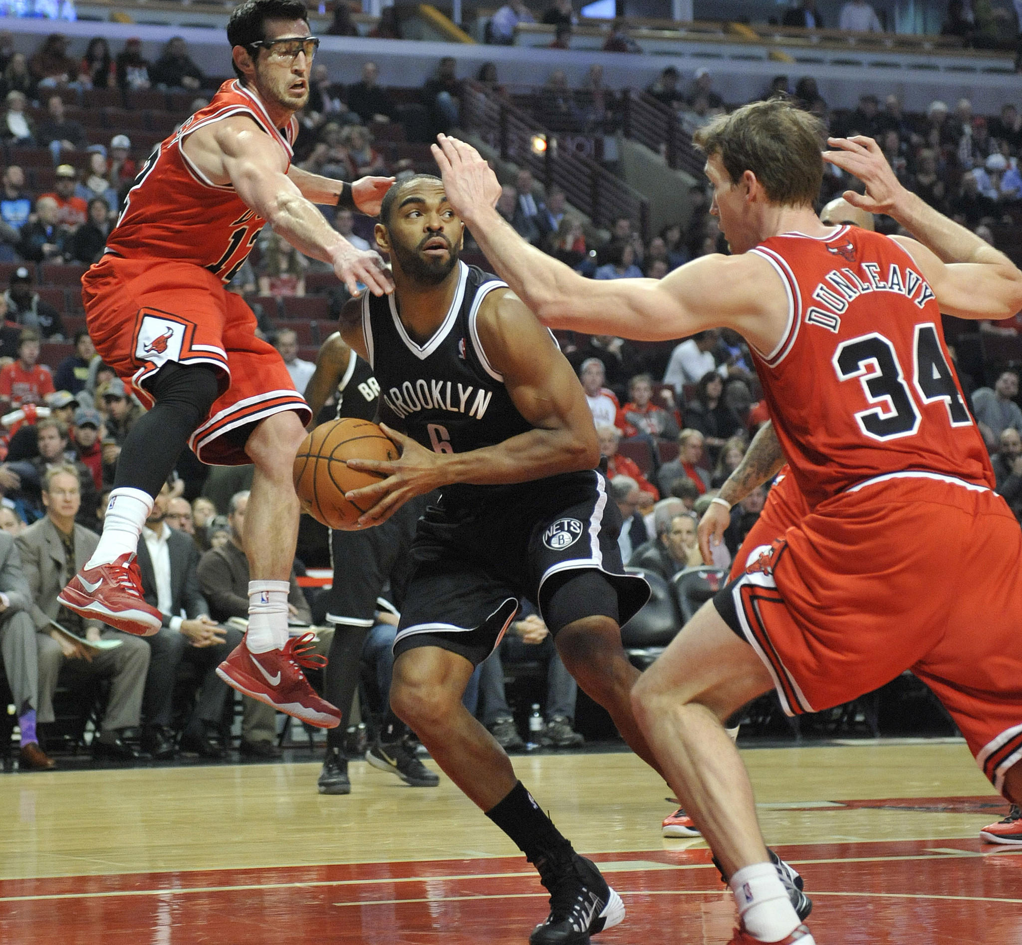 The Nets' Alan Anderson is defended by Kirk Hinrich and Mike Dunleavy during the first quarter at the United Center.