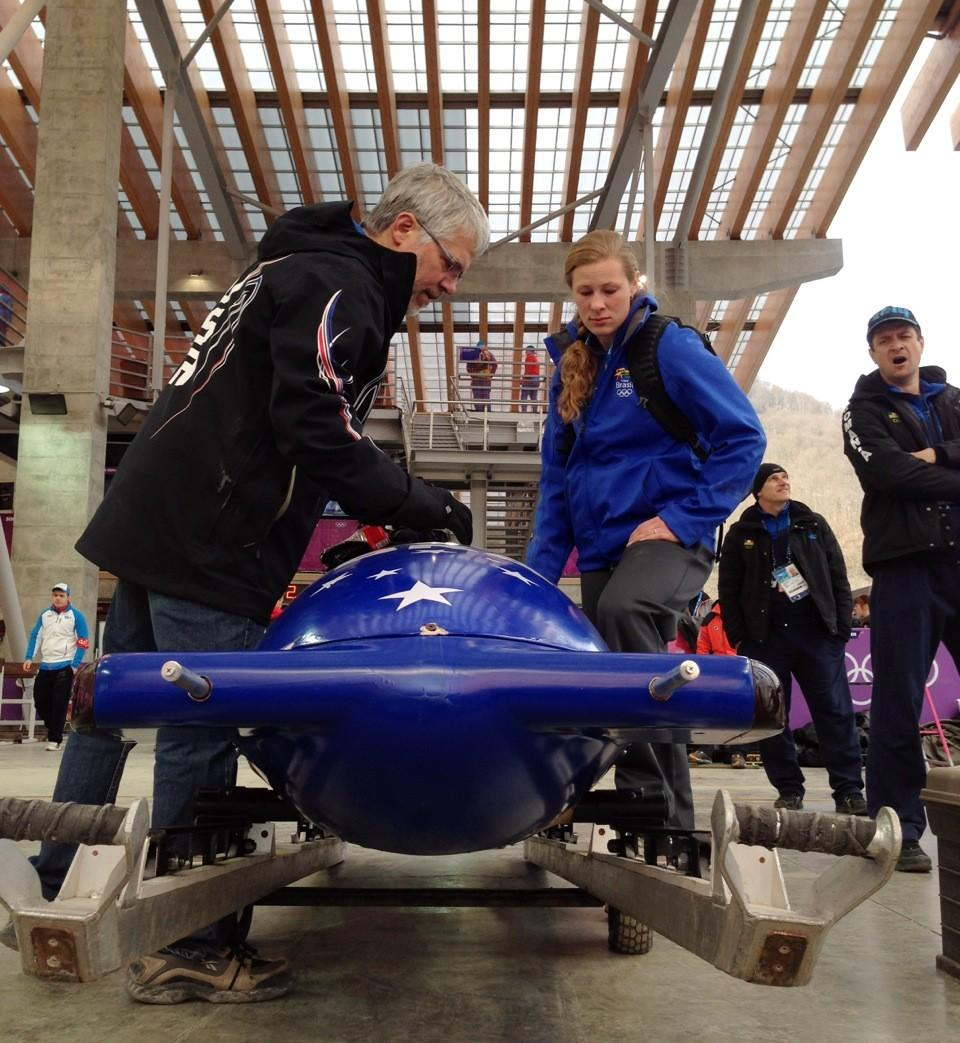 A Team USA coach helps Brazil look over their sled after a crash during training at the Sanki Sliding Center.