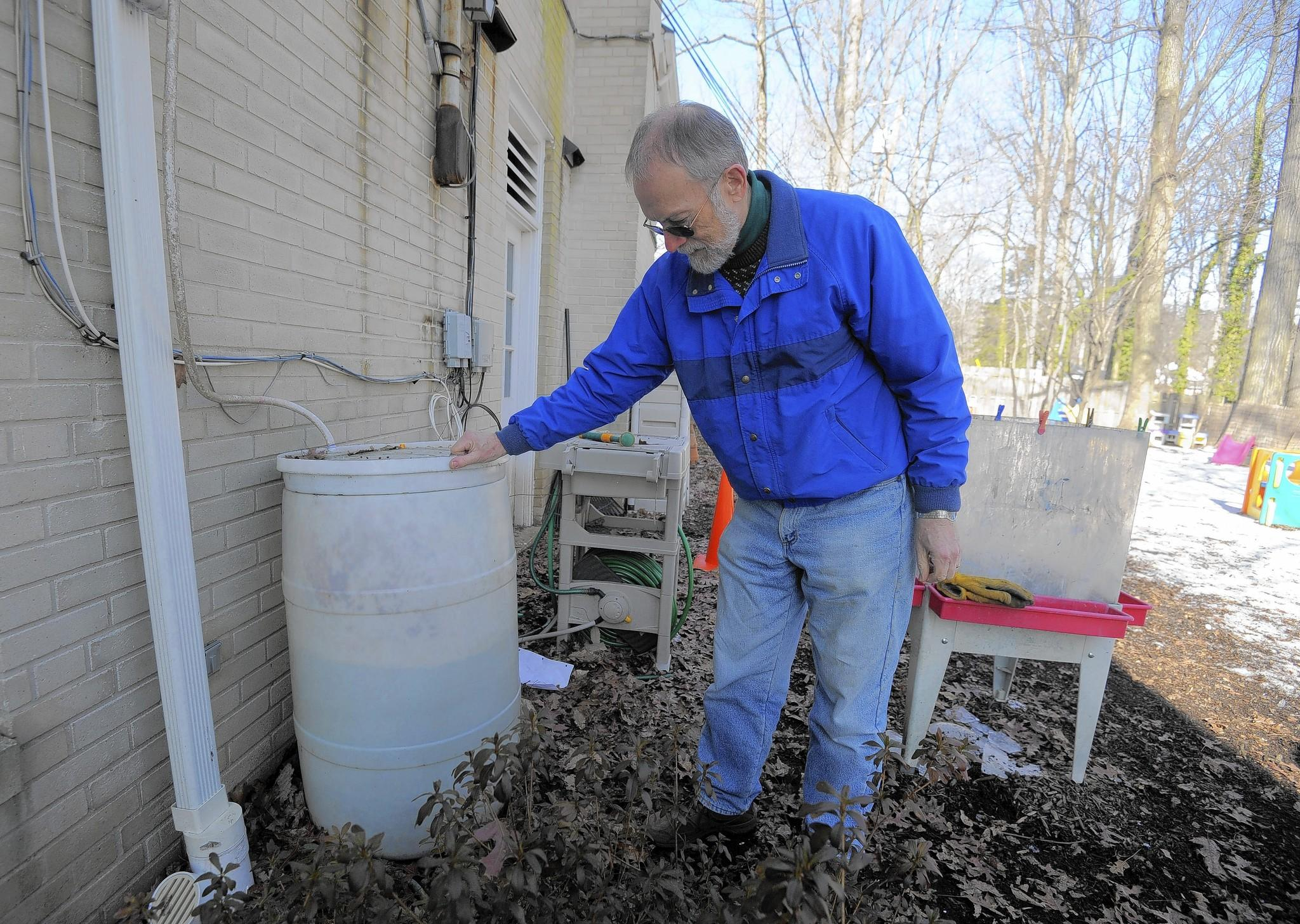 Bill Breakey, a member of Maryland Presbyterian Church's Environmental Stewardship Action Group, shows one of the rain barrels outside the building. This is one of the ways the church has been active in helping to reduce stormwater runoff.