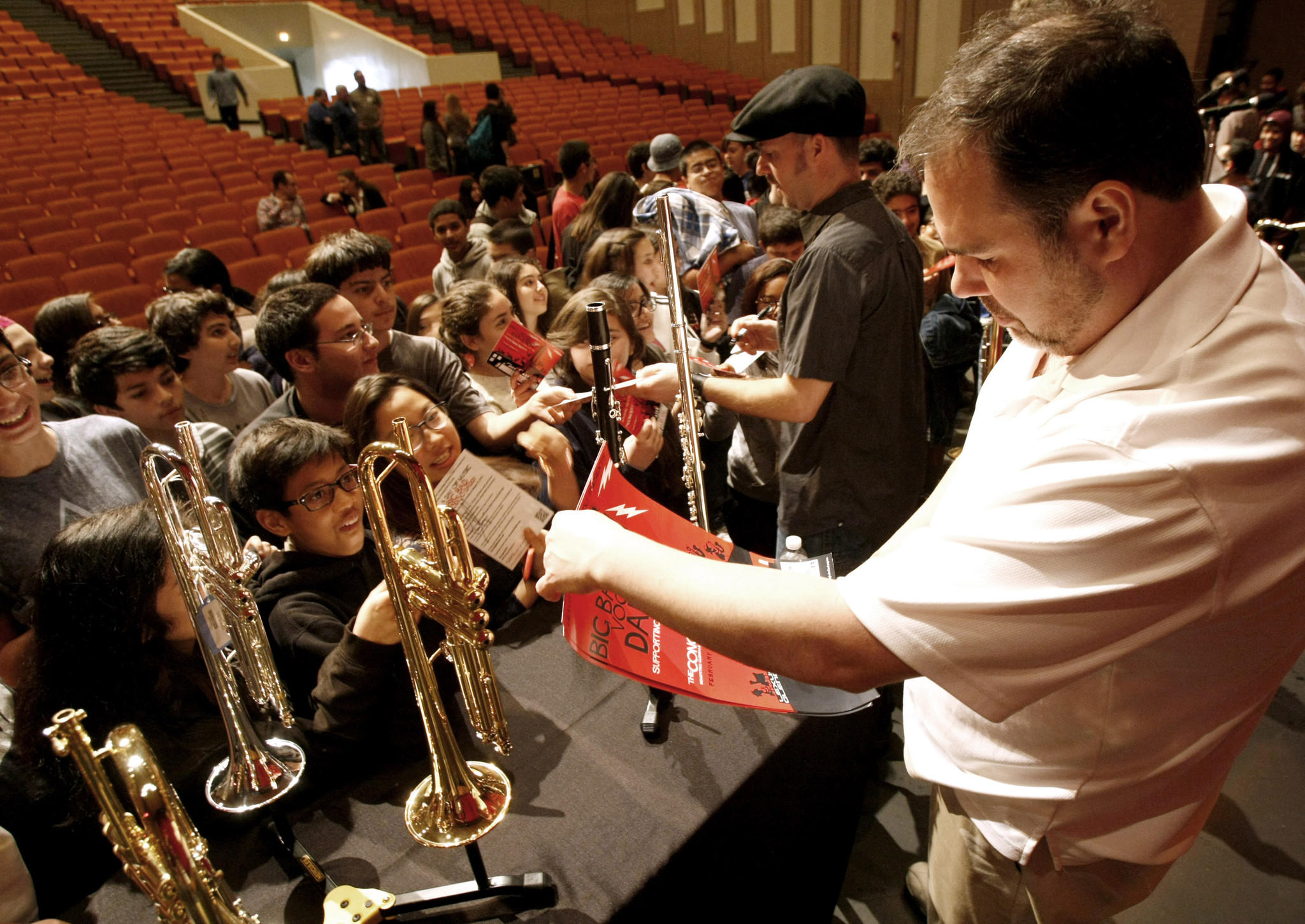 Members of the Big Bad Voodoo Daddy horn section Glen Marhevka, center, of Glendale, and Anthony Bonsera, right, sign autographs for local high school and junior high students after giving a clinic on playing music, at Glendale High School on Tuesday, Feb. 18, 2014. The band will perform a fundraising concert at the Alex Theater in a few days to benefit music and arts at Glendale schools.