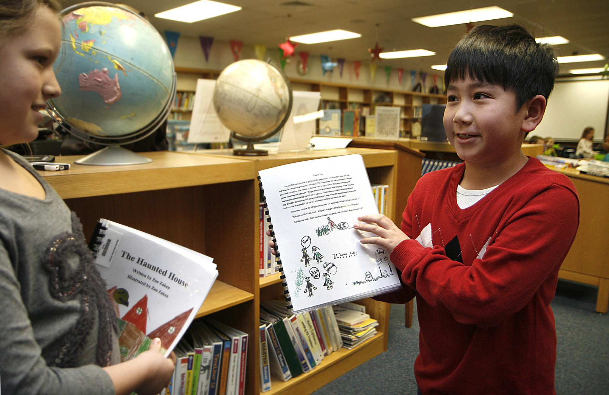 "Magruder Elementary has a program that publishes students' work into books, then places them in the library for other students to check out. Peter Dang, right, shows his book, ""The Lonely Children"" to fellow author Zoe Zaken, who wrote, ""The Haunted House""."