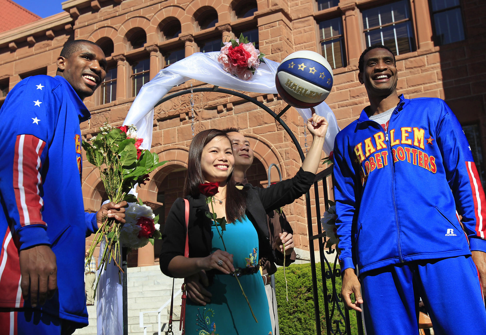 "Harlem Globetrotters' Wun ""The Shot"" Versher, far right, and Corey ""Thunder"" Law, far left, pose for photos with couple Michelle Doan, 31, center, and Binh Nguyen, 39, center right, after they were married on Valentine's Day at the Old Orange County Courthouse in Santa Ana."