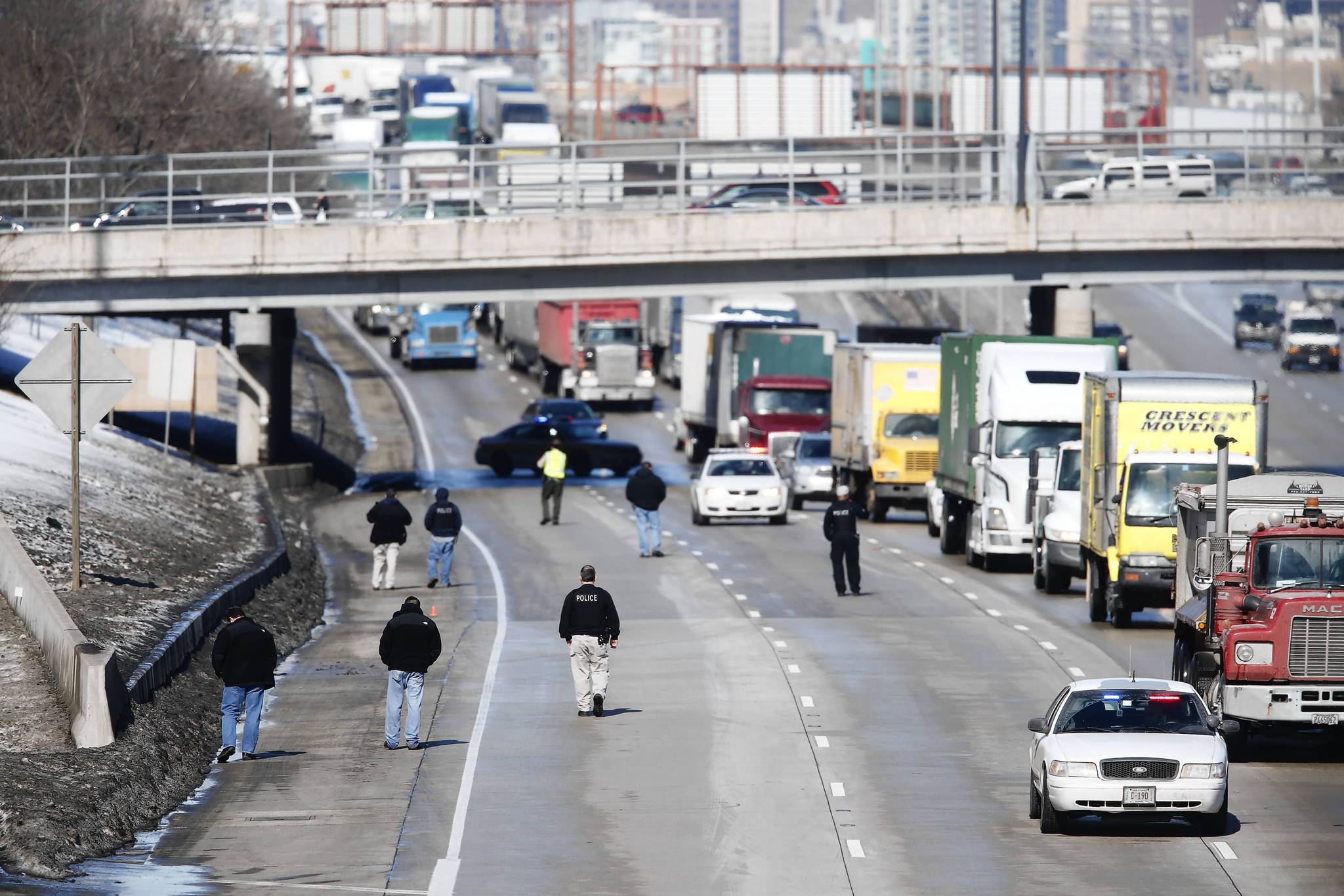 Law enforcement officials look for evidence on the Dan Ryan Expressway between the 31st Street and 35th Street ramp near a sight where police investigate a shooting following a chase.