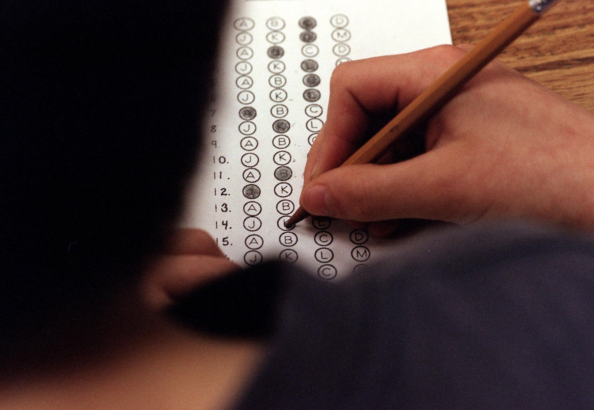 File photo: Student filling in answers on a standardized test. New research suggests high school grades are a better predictor for college success than SAT scores.