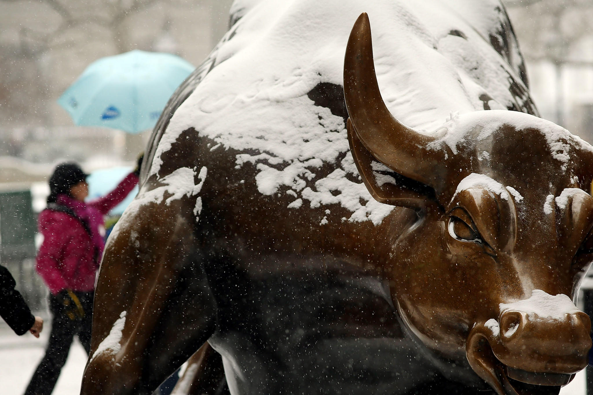 The Wall Street bull is dusted with snow during a snowstorm that moved through the Northeast in January 2014.