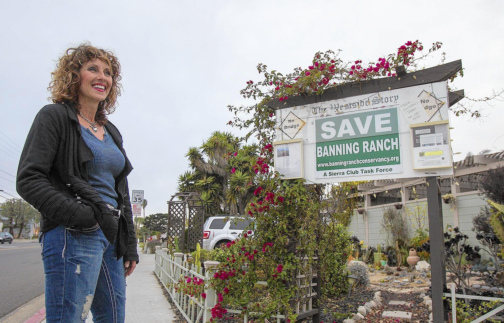 "Michelle Simpson stands by a sign in front of her West 19th Street home in Costa Mesa in January. The sign says ""The Westside Story"" and is a kind of meeting space and distribution center for neighborhood pamphlets."