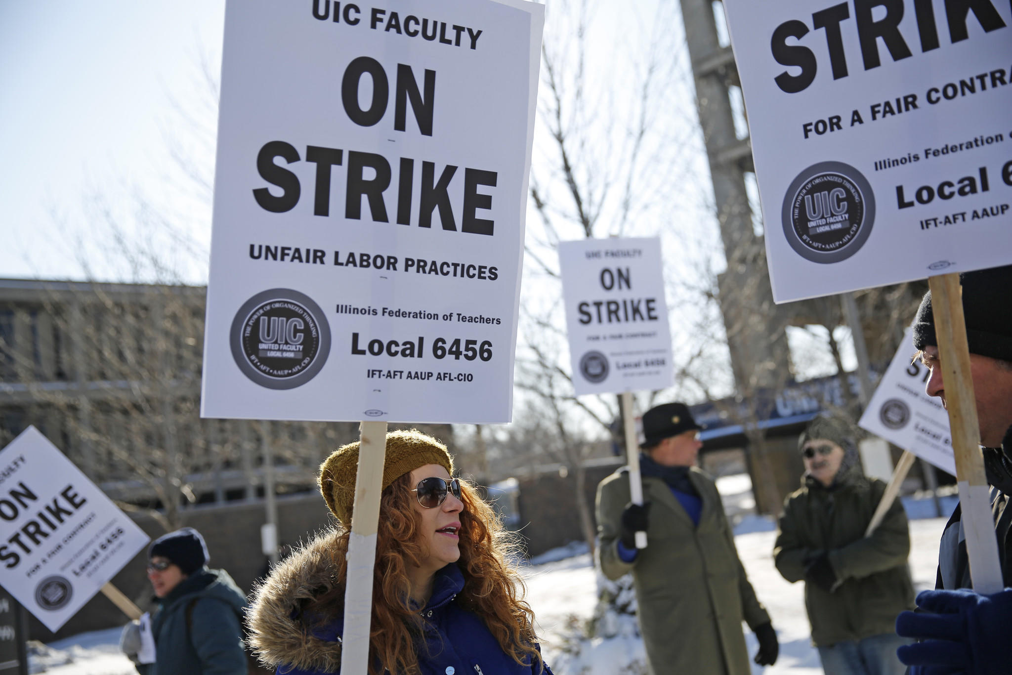 Jennifer Lewis, left, a lecturer in the English department at the University of Illinois at Chicago, chats with Jay Shearer, visiting lecturer in the English department, as they join other picketers near University Hall on the east campus of UIC on Tuesday.