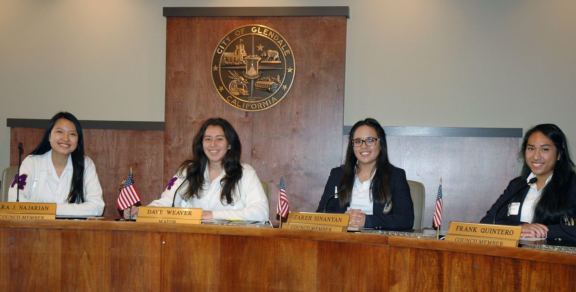 Holy Family High School students try out the City Council members' seats during a recent job shadow day at Glendale City Hall. They are, from left, Alexa Faraon, ASB President Julyanna Mendez, Fabiola Flores and Maryam Eapen. (Photo by Joyce Rudolph)