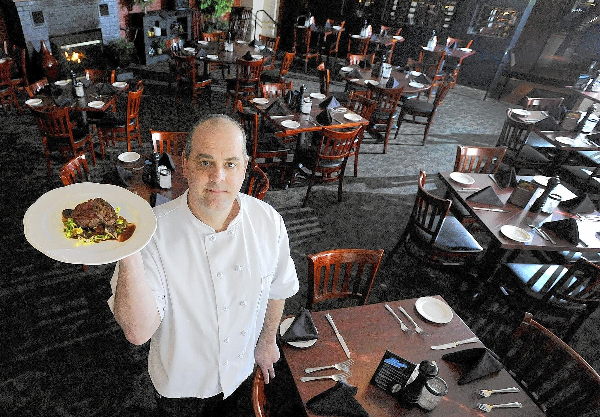 Marco Lombardini, new executive chef at the Grille at Peerce's, holds a seared beef tenderloin, served with mushrooms, brussell sprouts, diced baby potatoes and a red wine sauce, in the restaurant's Phoenix dining room Feb. 12.