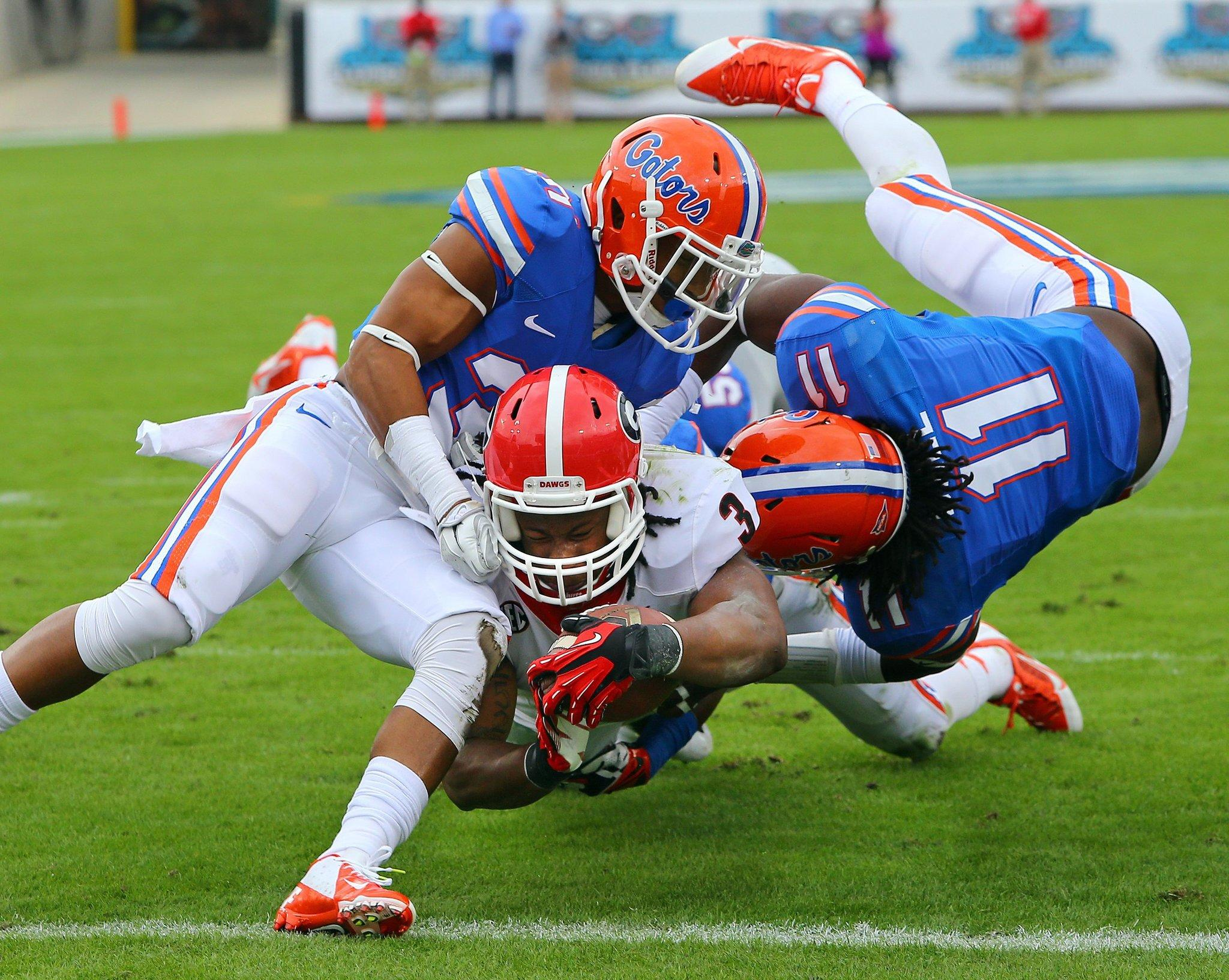 Georgia tailback Todd Gurley plows his way into the end zone between Florida defenders Cody Riggs, left, and Neiron Ball, right, during the first quarter at EverBank Field in Jacksonville, Fla.