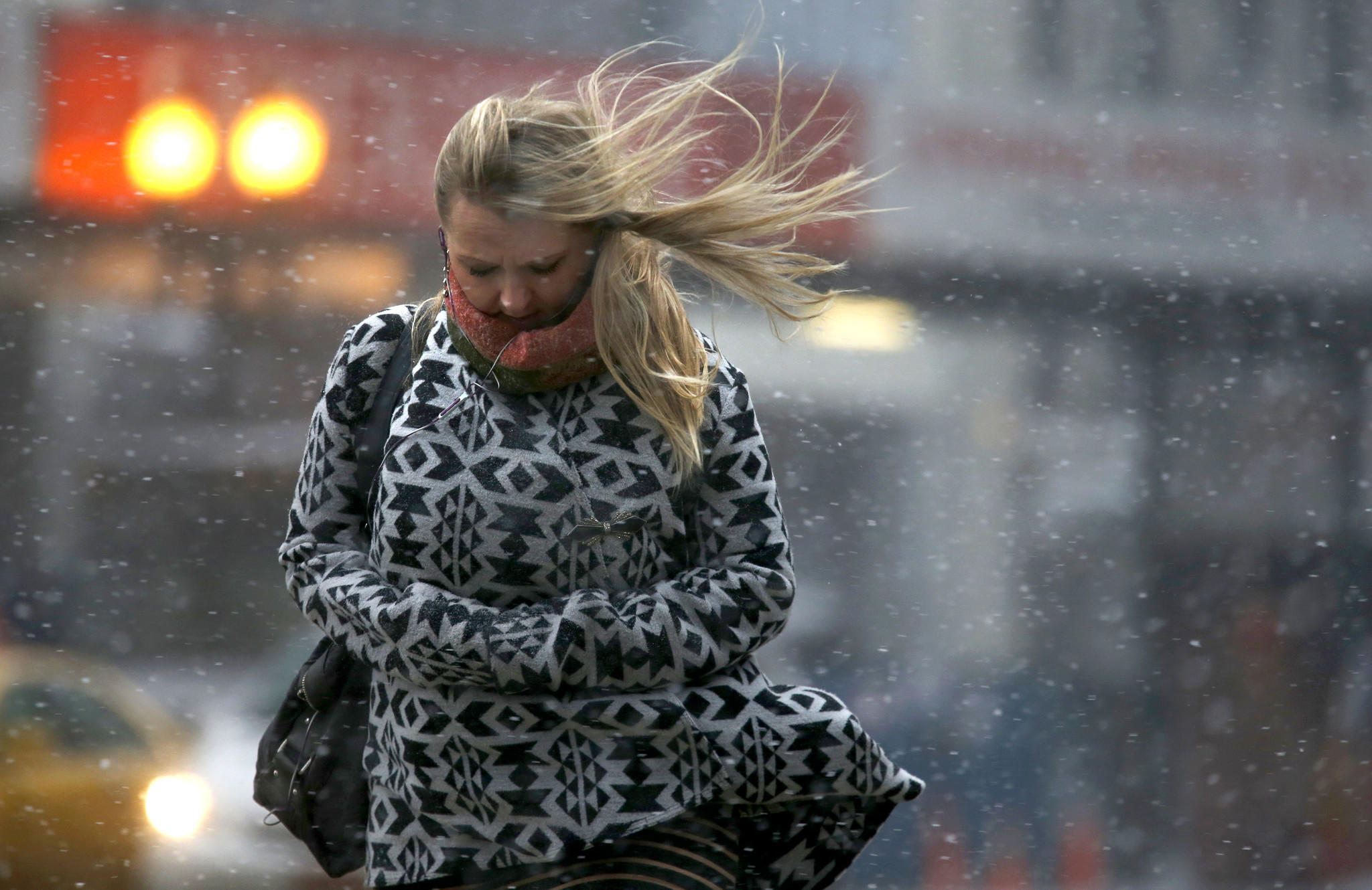A pedestrian crosses North Michigan Avenue at East Lake Street in Chicago's Loop as snow and high winds hit the area.