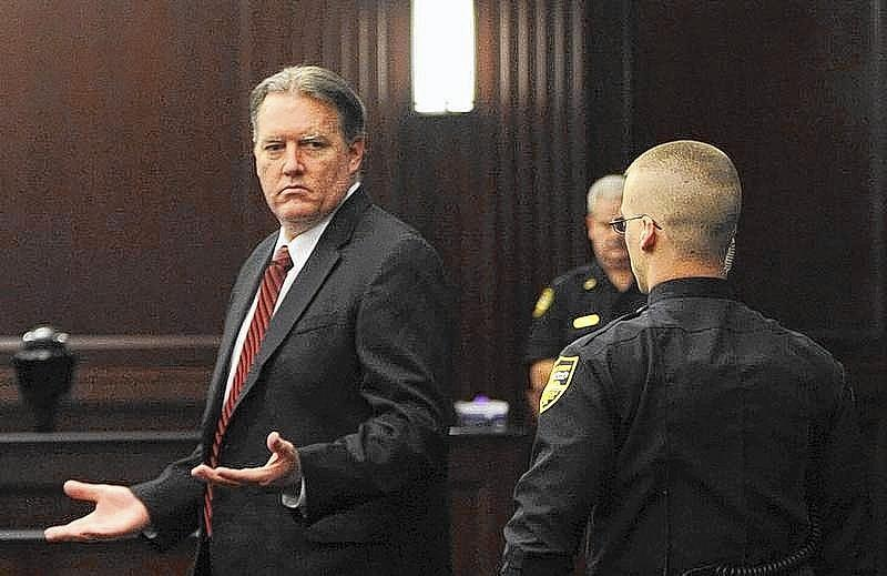 Michael Dunn raises his hands as he looks toward his parents after the verdicts were announced in his trial in Jacksonville.