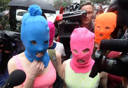 Wearing masks, members of Russian punk group Pussy Riot, Nadezhda Tolokonnikova (L) and Maria Alyokhina (C) speak to journalists while leaving the police station of Adler, near Sochi, on Feb. 18, 2014 after her arrest earlier in the host city of the 2014 Winter Olympics. Tolokonnikova and Maria Alyokhina walked free after being questioned about an alleged theft from a hotel.