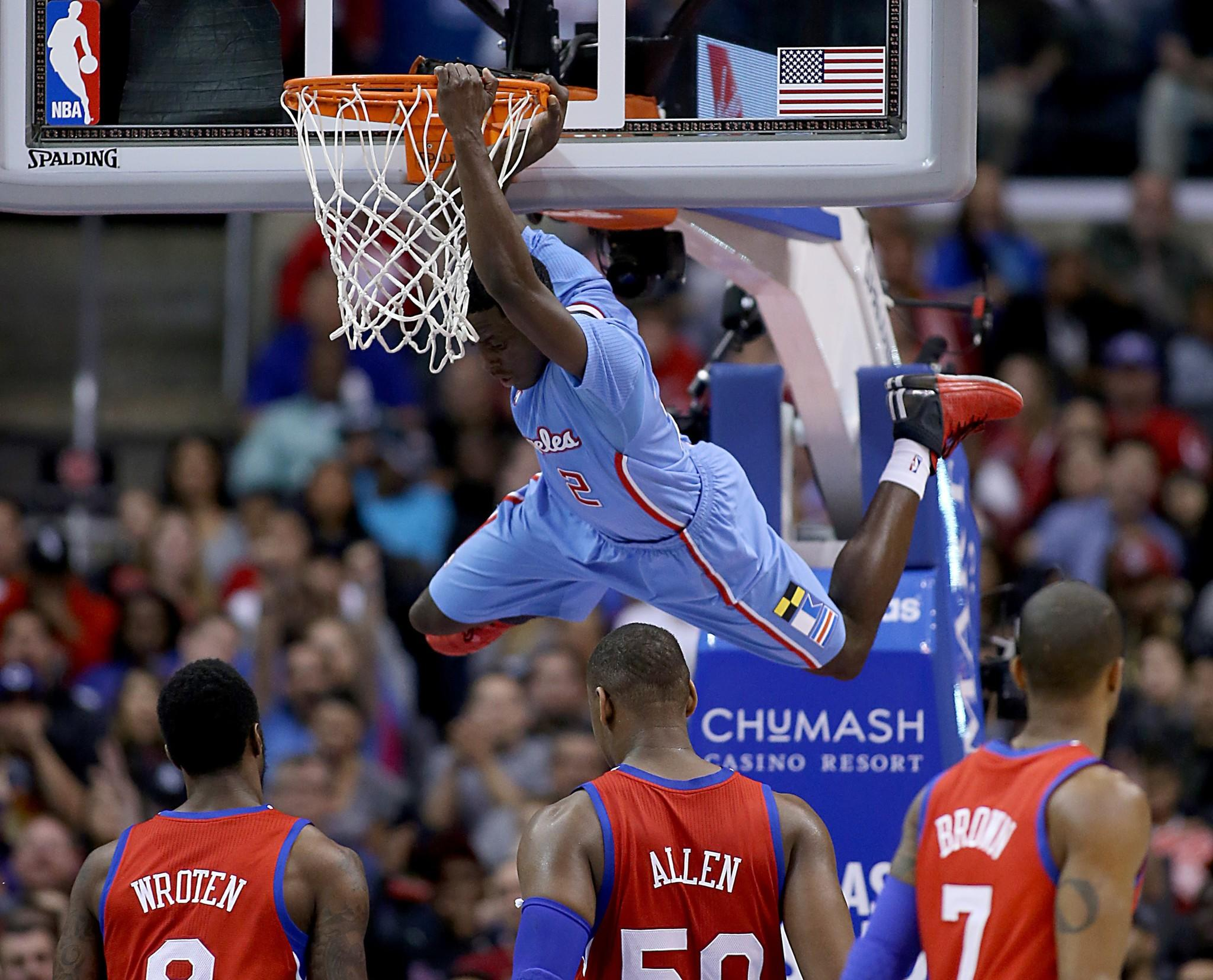 Darren Collinson hangs on the rim after cutting through the Philadelphia 76ers defense for a dunk during the Clippers' 123-78 victory at Staples Center.