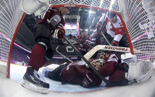 Kristaps Sotnieks of Latvia reaches over goalkeeper Kristers Gudlevskis for the puck during the third period of the Men's Ice Hockey Quarterfinal Playoff against Canada on Day 12 of the 2014 Sochi Winter Olympics on Feb. 19 in Sochi, Russia.