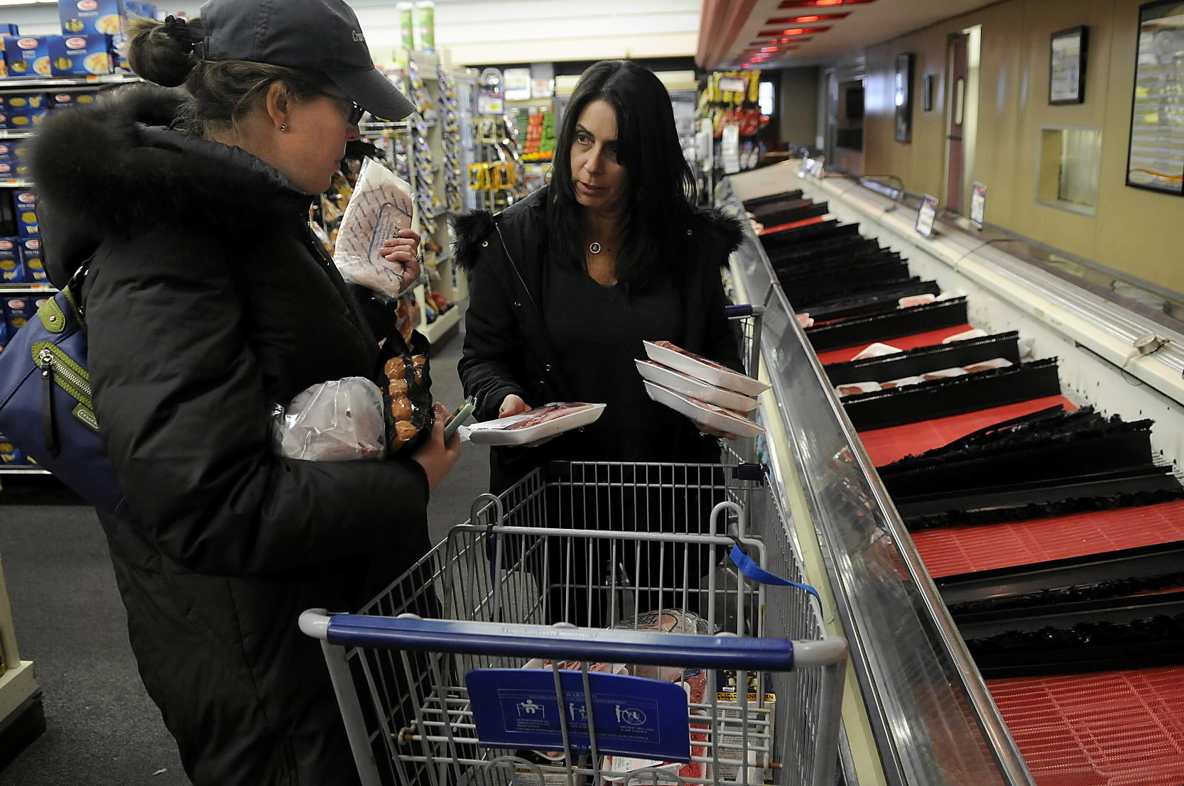 Betsy Marantz of Glastonbury, left, and Ellen Rosenberg of Simsbury collaborate on which meats each will take while shopping in at Crown Market in West Hartford on Wednesday afternoon.