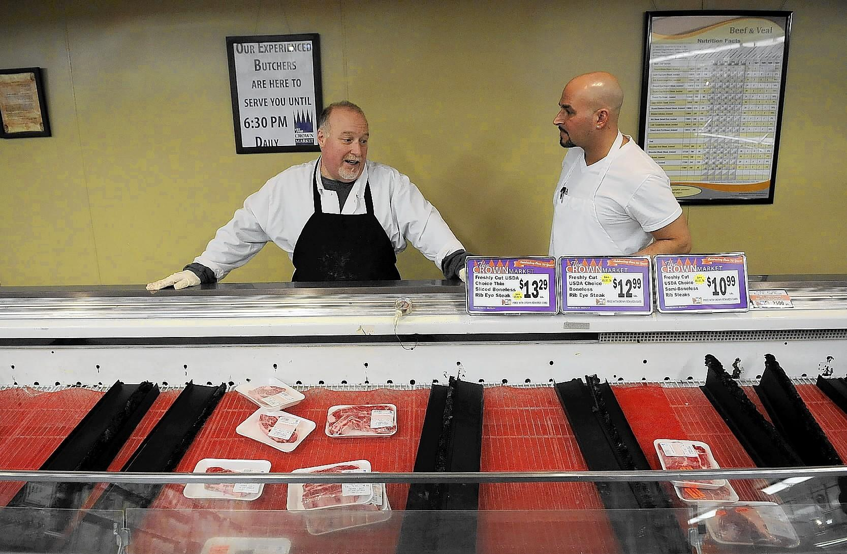 (L to R) Tom DeForge, meat department manager, and Matt Arsenault, deli chef, chat with one another about how they are unable to keep up with the demand for meats and prepared foods for their customers at Crown Market in West Hartford after it was announced earlier this week that they will close their doors for good around February 28.