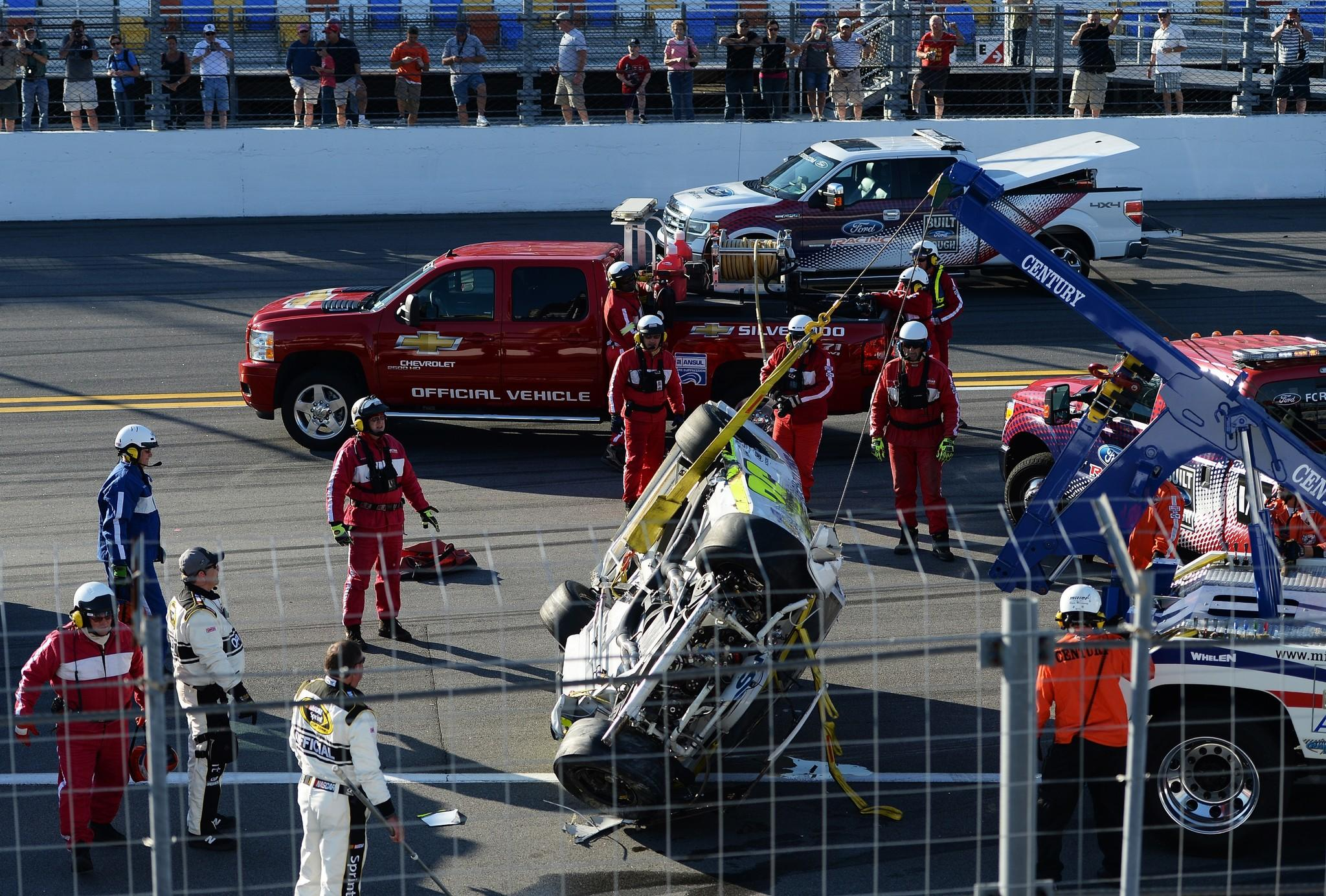 Parker Kligerman's No. 30 Swan Energy Toyota is flipped back over by safety crew members Wednesday after an incident during practice for the NASCAR Sprint Cup Series Daytona 500 at Daytona International Speedway.
