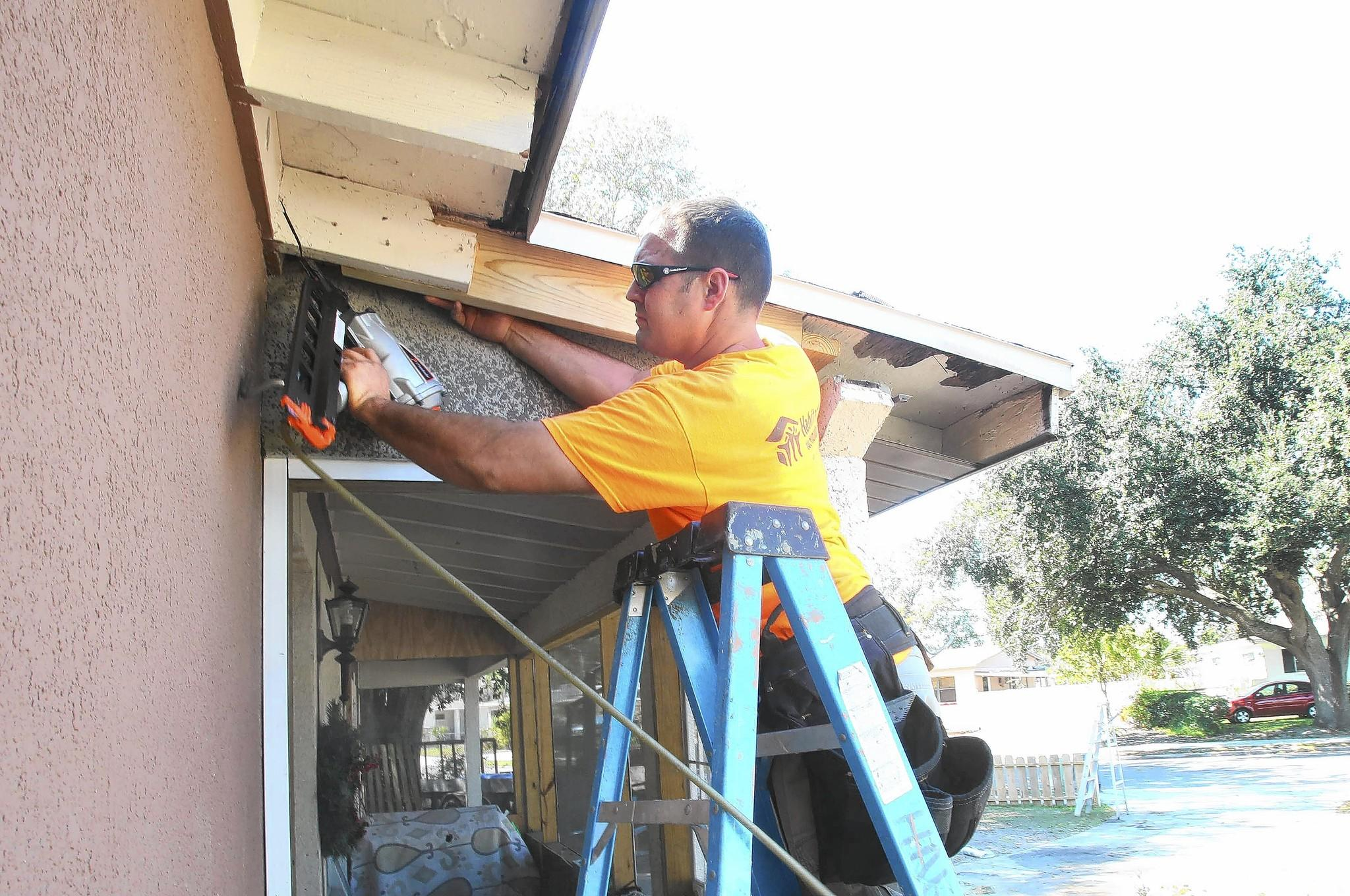 Mark Myrick from Habitat for Humanity repairs eaves on a house in Pine Hills ahead of the volunteers who will do painting. Feb. 19, 2014 B583543568Z.1 George Skene/Orlando Sentinel