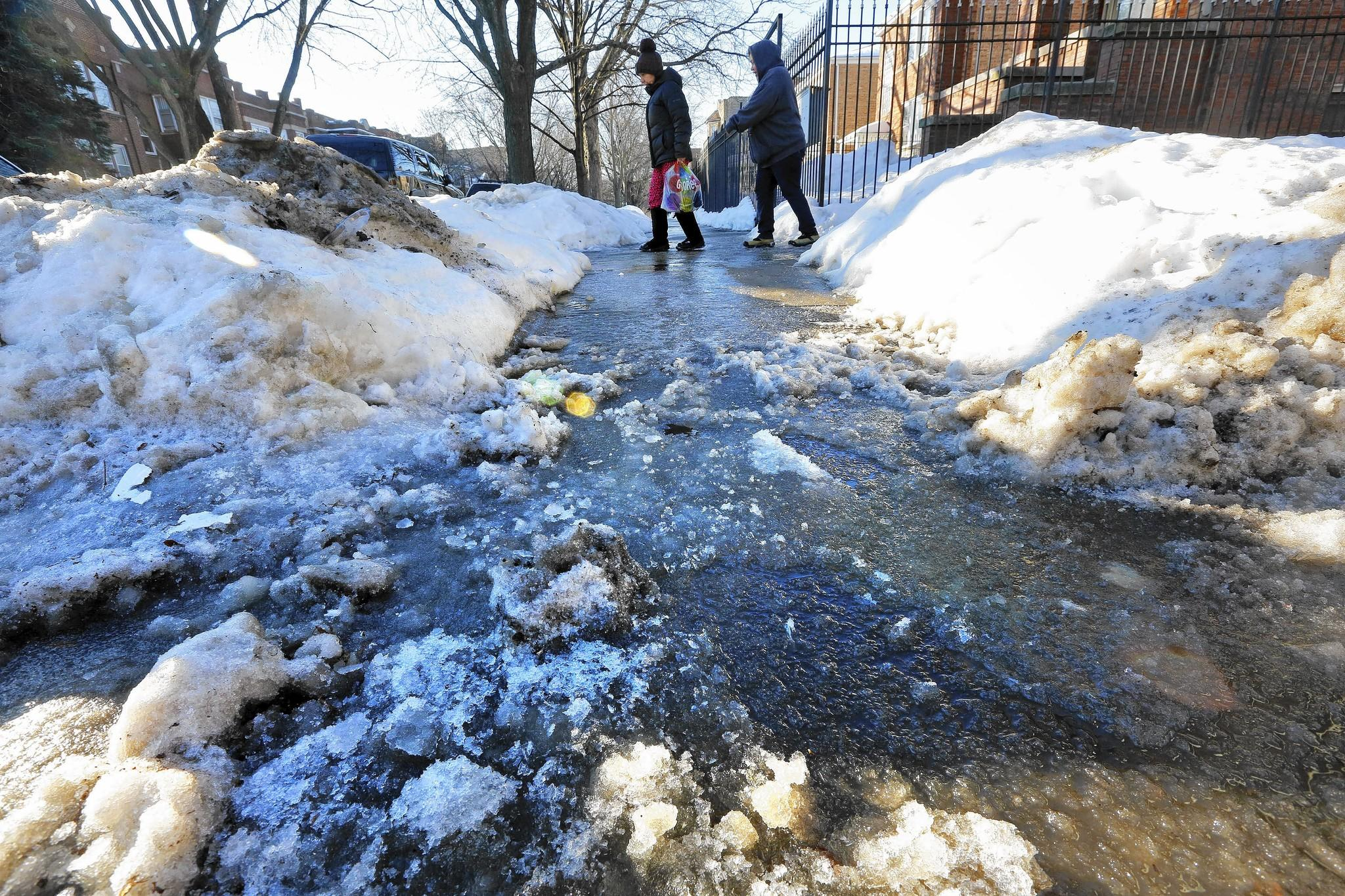 Two pedestrians walk on an icy sidewalk near a large puddle of water in the Albany Park neighborhood.