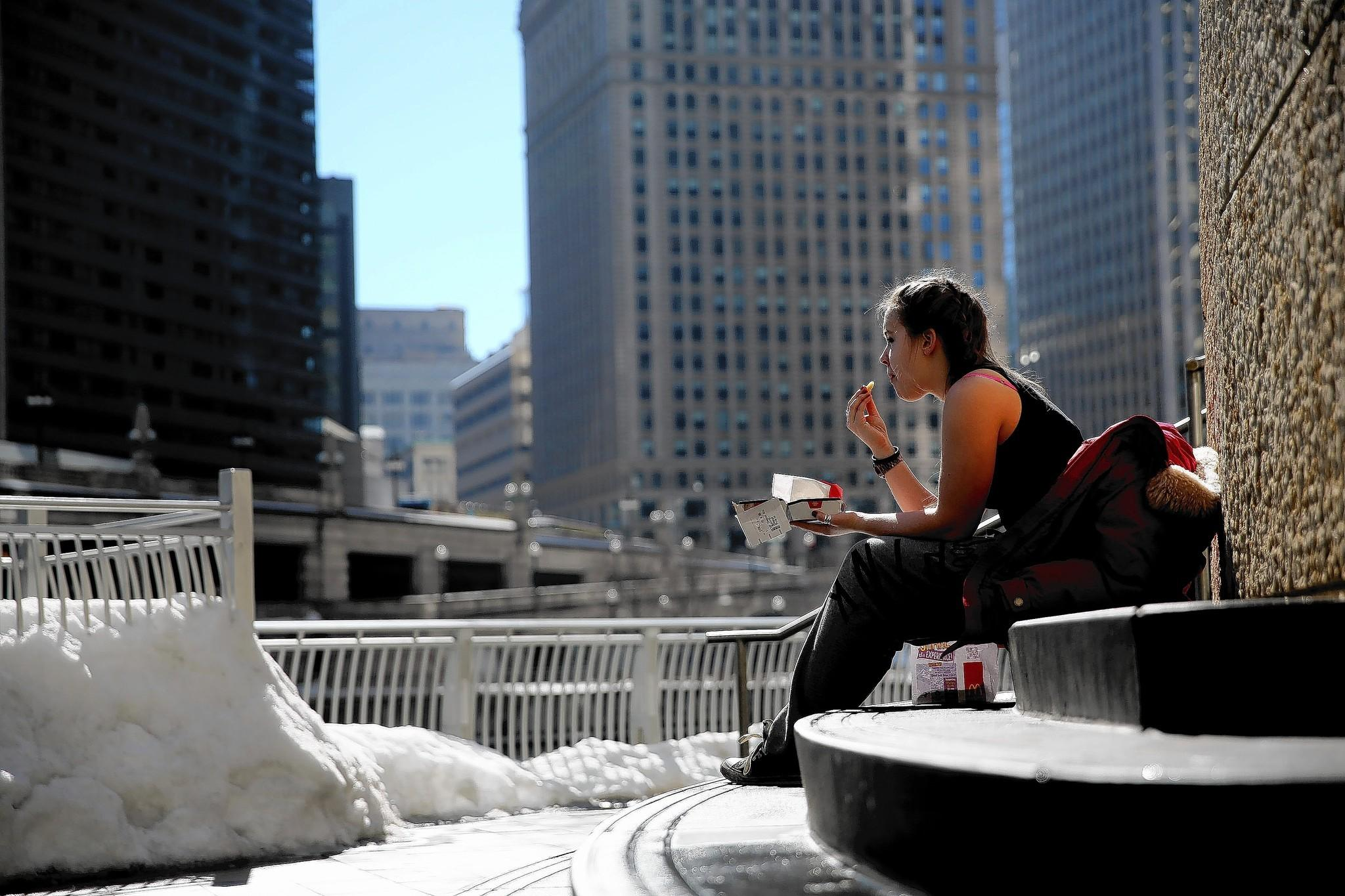 Holly Haynes, 16, of London, lunches amid Wednesday's fleeting good weather at Trump Plaza in Chicago.