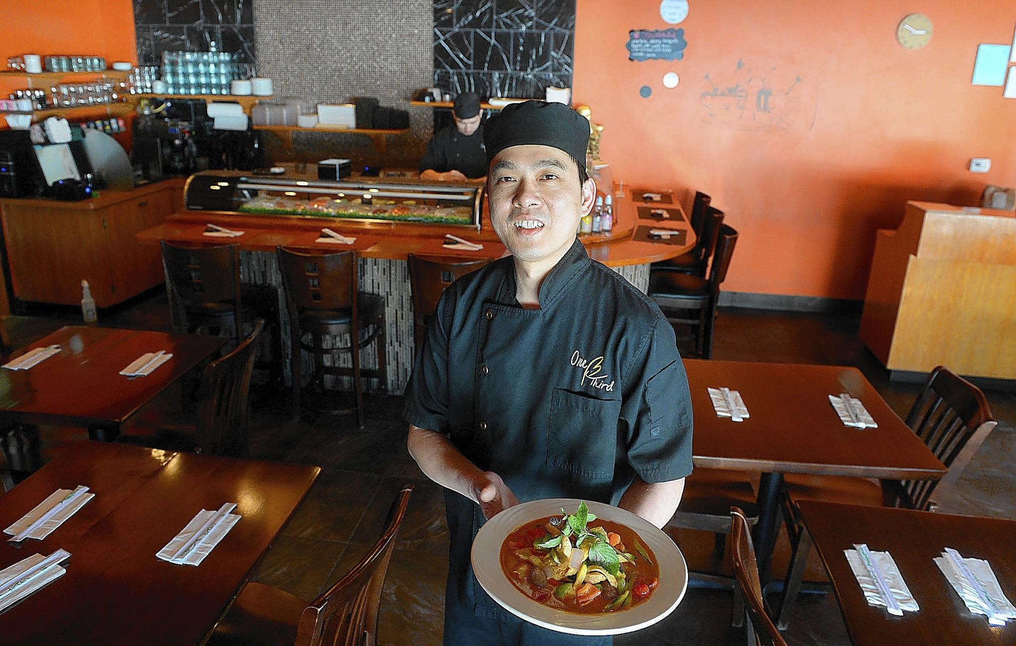 Kenny Lin, owner-chef of One Third Asian Cuisine Sushi and Grill located in Bethlehem, holds a plate of Thai Red Curry Chicken.