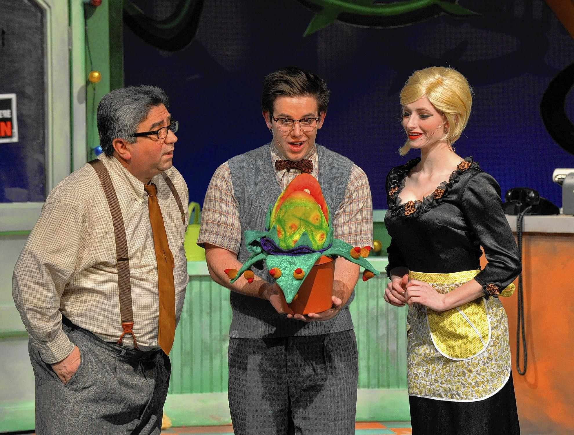 (L to R) Nick Englesson, Kevin Riddagh and Jessica Minor look at Audrey II in Cedar Crest's Little Shop of Horrors.
