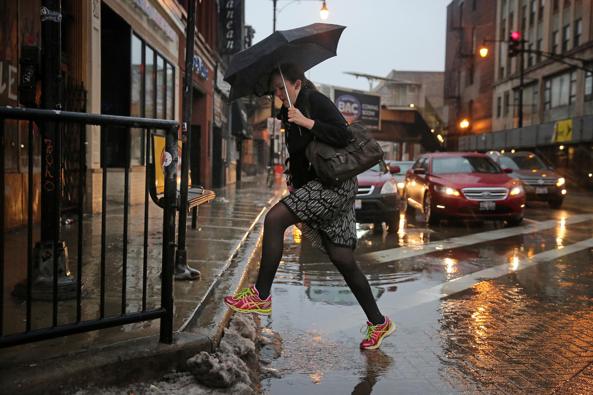 A woman avoids a large puddle at North and Milwaukee Avenues in Wicker Park.