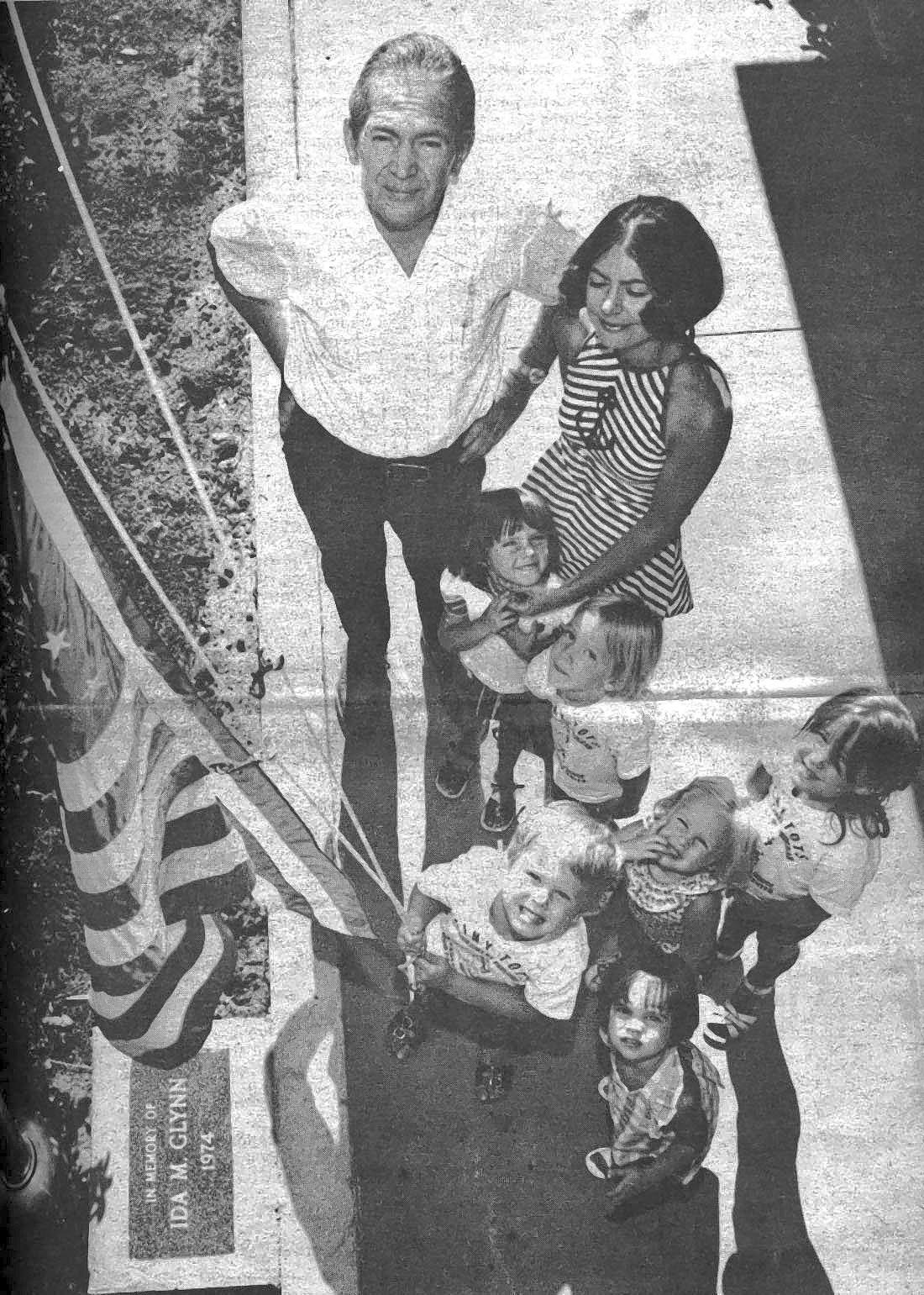 In 1974 the Ida M. Glynn Memorial Fund purchased a new flagpole for the La Cañada Youth House (today the Community Center of La Cañada Flintridge). A brass plate bearing her name is set in marble at the flagpole?s base. Ida Glynn, who with her husband, Ed (standing at the top of the photo) operated the La Cañada Variety Store, was beloved in the community. Her children, grandchildren and now great-grandchildren have taken part in programs at the center over the past decades. Shown with Ed Glynn admiring the flagpole are members of the Tiny Tots preschool program and their teacher, Pat Yunker.