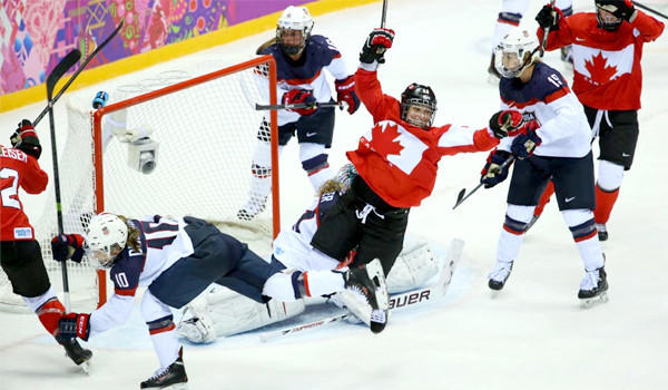 Marie-Philip Poulin of Canada, center, celebrates after scoring the game-winning goal in overtime to snatch the gold medal away from the United States after overcoming a 2-0 deficit in the third period to push the game to sudden death.