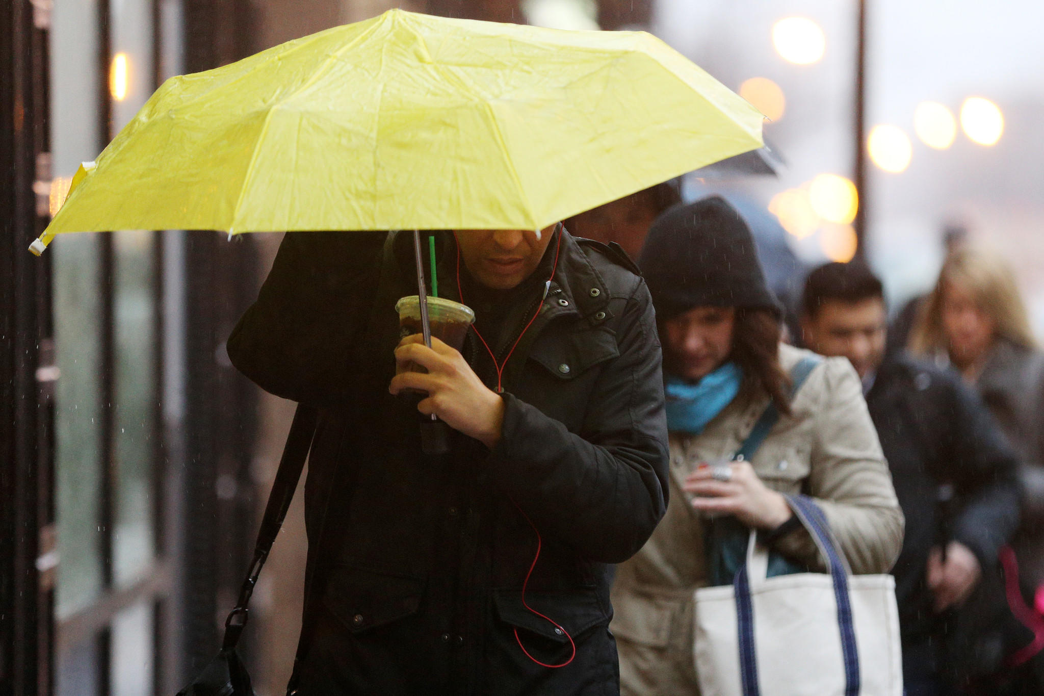 Commuters juggle coffee and umbrellas in the sloppy weather.