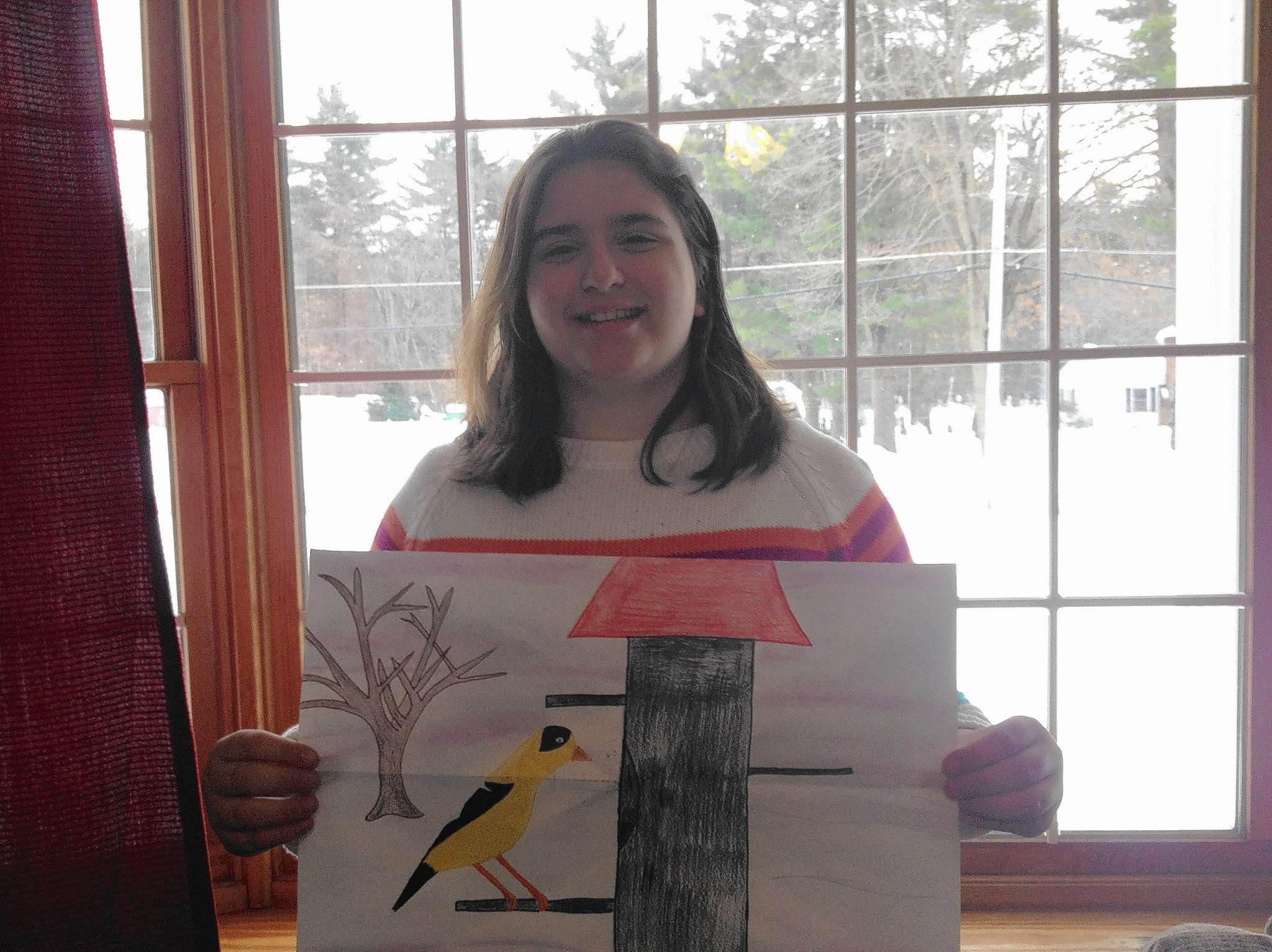 Christina Swider, an 11-year-old sixth grader at John F. Kennedy Middle School, holds her drawing of a goldfinch that won her an award in Cornell's Celebrate Urban Birds Fascinating Feathers art competition.