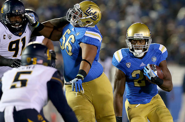 UCLA offensive lineman Xavier Su'a-Filo (56) creates a running lane for tailback Paul Perkins during a game against California last season.