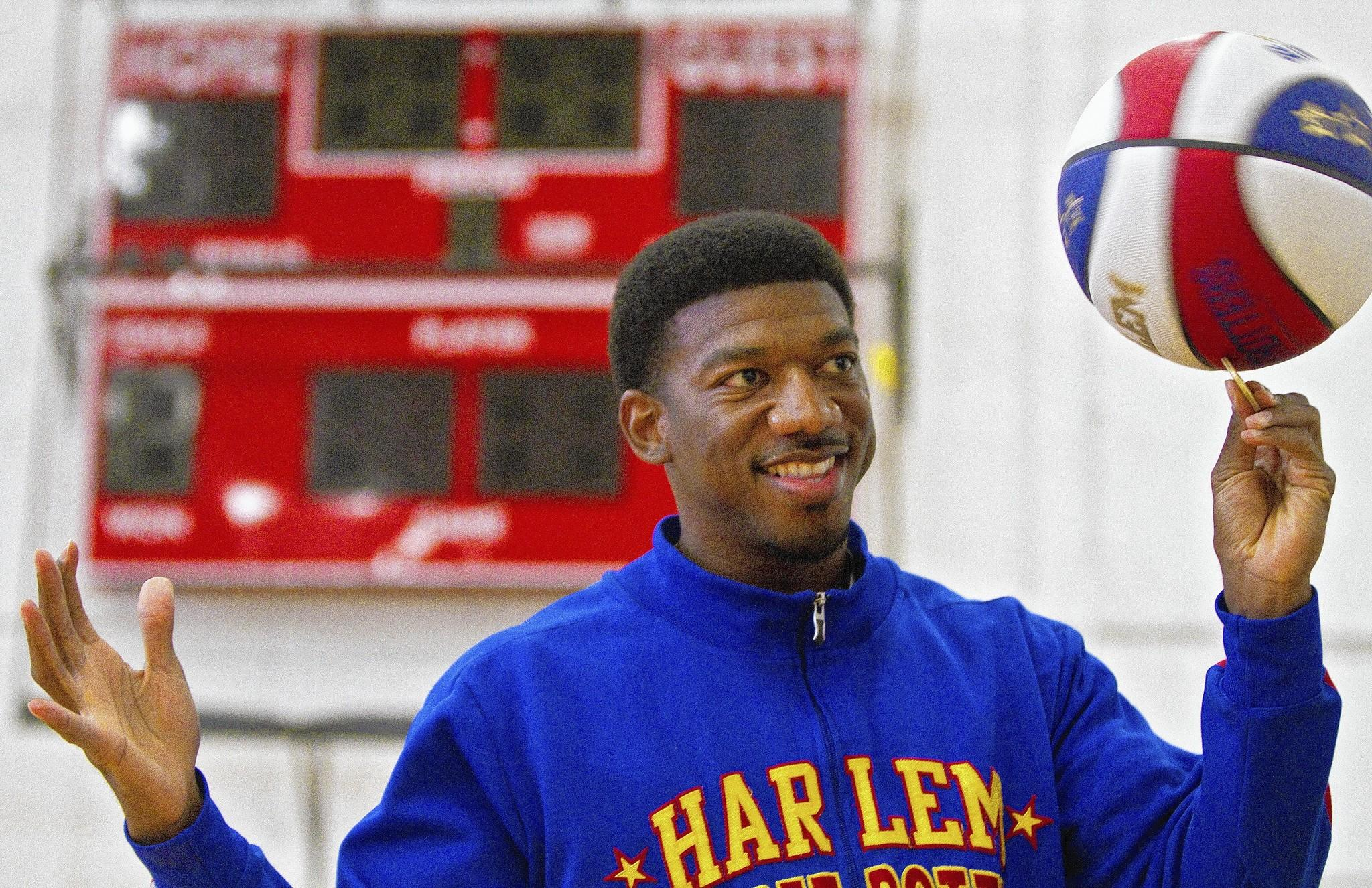 "Harlem Globetrotters player Anthony ""Buckets"" Blakes spins a basketball while posing for a photo on Thursday at Huntington Hall."
