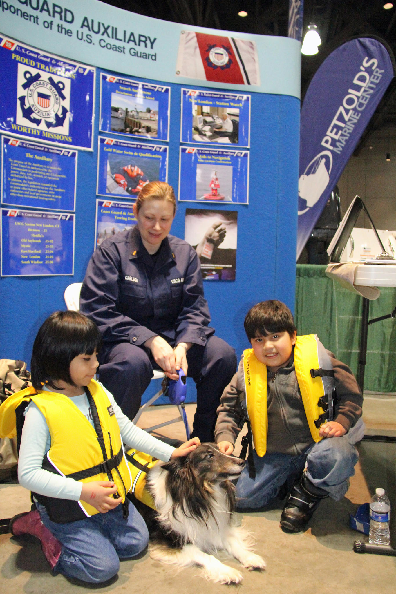 USCG Auxiliarist Kristina Carlson, center, keeps an eye on Remmie, her eight year old Sheltie, and mascot of the United States Coast Guard Auxiliary.