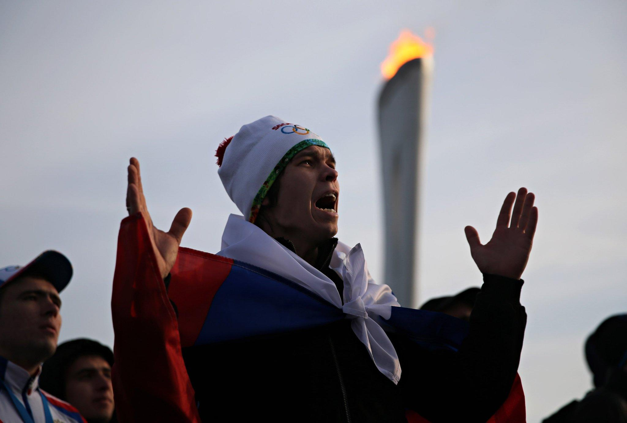 A fan wearing a Russian flag in Olympic Park reacts during Russia's 3-1 loss to Finland.