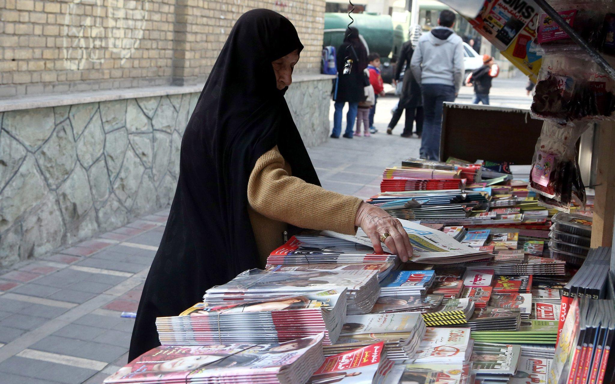 An Iranian woman looks at newspapers displayed at a kiosk in a Tehran street in January.