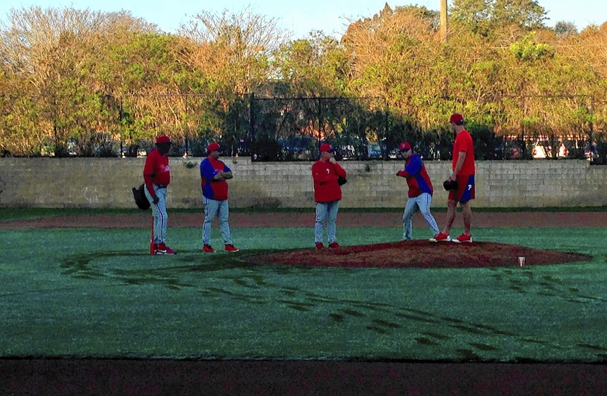 Phillies pitcher Jonathan Pettibone on the mound early Thursday morning working on mechanics while coaches watch. At Phillies spring training in Clearwater.